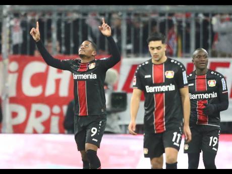 Leverkusen's Leon Bailey (left) celebrates after scoring the opening goal during the German Bundesliga match between FC Bayern Munich and Bayer Leverkusen 04 in Munich, Germany, yesterday. Bailey scored both goals in Leverkusen's 2-1 win.