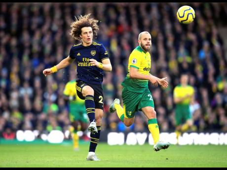 Arsenal's David Luiz (left) and Norwich City's Teemu Pukki in action during their English Premier League match at Carrow Road in Norwich, England, yesterday.AT RIGHT: Arsenal's interim head coach Freddie Ljungberg reacts on the touchline during the match yesterday.