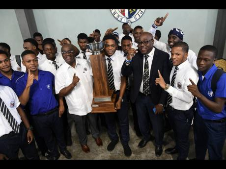 Jamaica College principal Wayne Robinson (second left), team captain Tyrese Small (centre),  team manager Ian Forbes (third right), and other Small's teammates celebrate with the Manning Cup trophy at the Karl Hendrickson Auditorium on the school grounds yesterday.