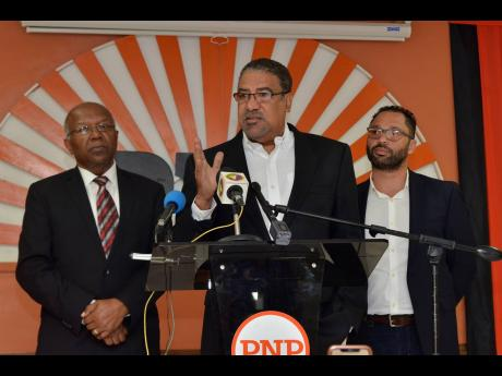 Opposition Shadow Minister of Tourism Dr Wykeham McNeill (centre) is flanked by health spokespersons Drs Morais Guy (left) and Shane Alexis at the PNP's Old Hope Road headquarters.