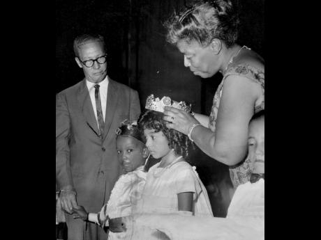 Una Marson, founder of the Jamaica Save the Children Foundation, crowns May Queen Debra Lyn Keisse at the Children's concert held at the Ward Theatre on May 5, 1964. The May King, Horace Mesquita, is wearing his crown, which was presented by the deputy mayor, Councillor Wesley Shirley (left).