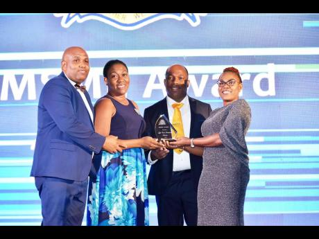 From left: Enock Gooden, Francene Gooden, and Conroy Ghans of Lifecall Ambulance accept the Micro Small & Medium Enterprises Award from director of the Montego Bay Chamber of Commerce Julian Palmer.