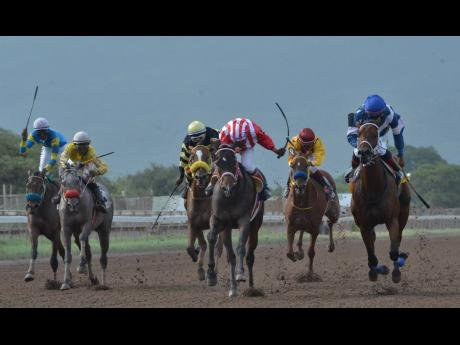 CRYPTOCURRENCY (centre), ridden by Ian Spence on his way to victory in the Titania Trophy over 1100m at Caymanas Park in St Catherine on Saturday, July 6, 2019.