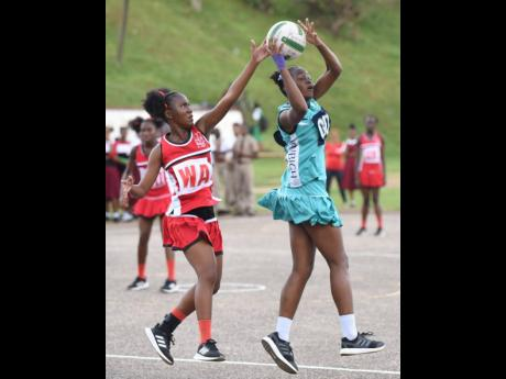 Shenae Melbourne (left) wing attack from Glenmuir High, tries to block a pass fromTamara Williams, goal defence from Denbigh High, during the ISSA Rural Area Schoolgirls Netball junior final on Thursday, December 5, 2019 at Manchester High School. Denbigh won 24-12.