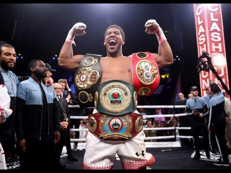 Britain's Anthony Joshua celebrates after beating  Andy Ruiz Jr. on points to win their World Heavyweight Championship contest at the Diriyah Arena, Riyadh, Saudi Arabia, yesterday.
