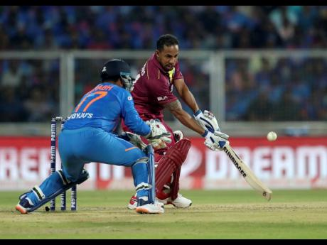 Windies' Lendl Simmons (right) plays a shot on his way to his first half-century in nearly four years during the second Twenty20 International cricket match against India in Thiruvanathapuram, India, yesterday.
