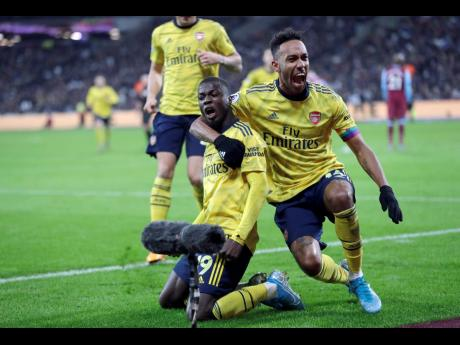 Arsenal's Nicolas Pepe (left) celebrates with captain Pierre-Emerick Aubameyang after scoring his side's second goal during their English Premier League match against West Ham United at the London Stadium in London, England, yesterday.