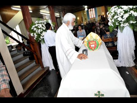 The Reverend Dr Robert Thompson pays his respects to the late Reverend Dr Alfred Reid at the mass of resurrection for the retired Bishop of Jamaica and the Cayman Islands at the Cathedral of St Jago de la Vega in Spanish Town, St Catherine, yesterday.