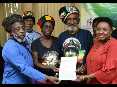 Culture Minister Olivia Grange (right) hands over the copy of the deed for the Coral Gardens Trust Fund to members of the Rastafari Coral Gardens Benevolent Society on Thursday. The members are (from left) Lewis Brown, Edward Fray, Pamella Williams and Isaac Wright. The deed was signed at a ceremony at the culture ministry in New Kingston.