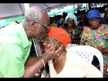 Desmond McKenzie, member of parliament for Kingston Western, kisses Daphne Weller at the West Kingston annual senior citizens' treat at the Tivoli Gardens Community Centre on Seaga Boulevard on Friday.
