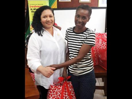 Edith Chin, co-owner and director of Juici Patties, hands a Christmas care package to May Pen Market vendor Verna Lewin at the Clarendon Municipal Corporation on Thursday, December 19.