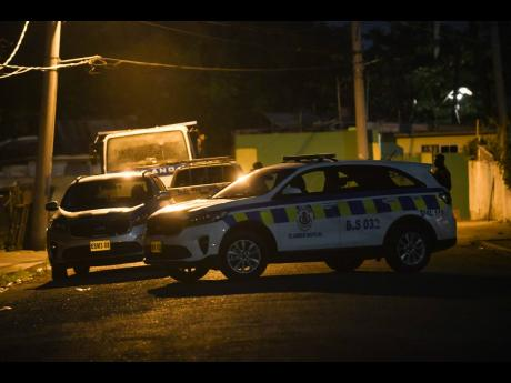 A police service vehicle blocks access along Bowens Road, in the vicinity of Waltham Park Road, where six people were hit in a drive-by shooting around 6:30 p.m. Up to press time, one woman was pronounced dead.