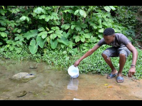 Joel gets water at the spring in the community  for his daily needs.