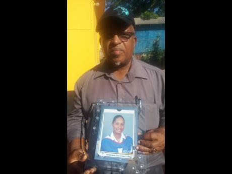 Neville Sinclair shows a photo of his daughter, Nevia, who was slain in Brinkley district, St Elizabeth, on Sunday night.
