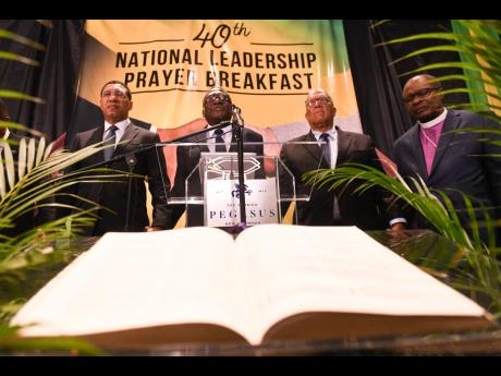 Prime Minister Andrew Holness (left) and Bishop Conrad Pitkin (second left), custos rotulorum of St James and pastor of the Faith Temple Assemblies of God in Montego Bay, pray with Opposition Leader Dr Peter Phillips (second right) and Reverend Stanley Clarke, chairman of the National Leadership Prayer Breakfast Committee, during the National Leadership Prayer Breakfast held yesterday at The Jamaica Pegasus hotel in New Kingston.