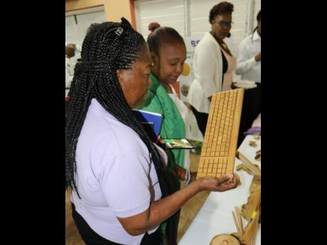 Claudia Griffiths takes a close-up look at the computer keyboard made from bamboo on display at yesterday's seminar on bamboo leaves, while her friend, Audrey Brown, checks out other items.