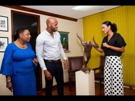 Sport Minister Olivia Grange (left) shares a light moment with Olympic sprinter Asafa Powell (centre), and wife, Alyshia, as they admire the maquette of the monument to be erected at the National Stadium in tribute to the runner.