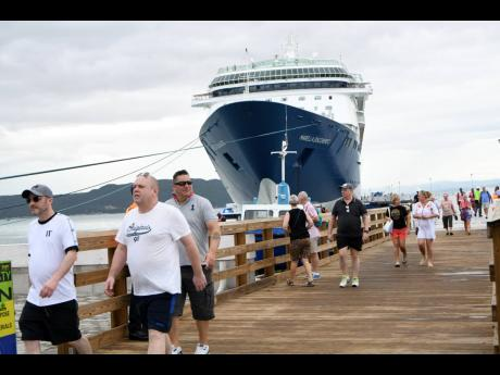 Tourists mill about at the Port Royal Cruise Ship Pier after the Marella Discovery 2 docked at the east Kingston town on Monday.