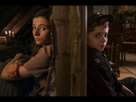 Jojo's (Roman Griffin Davis) life turns upside down when he finds out his mother is hiding a young Jewish girl (Thomasin McKenzie) in 'Jojo Rabbit'.