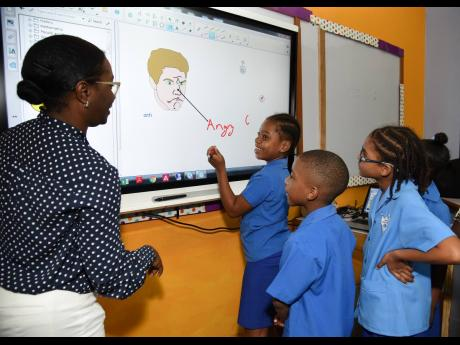 Jahssett Malcolm (left), senior accounts manager, Massy Technologies, shows students at the Port Royal Primary School how the interactive SMART board is used. Port Royal Primary and Infant School received US$10,000 through a grant from the Silicon Valley Charity Foundation to purchase the high-tech SMART board to enhance its information technology programme and improve the teaching and learning at the school.