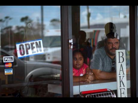 A man and girl peer out from a bakery and cafeteria in Freeport, Bahamas, on September 11 last year. Like the bakery, Bahamas remained open for business despite the ravaging impact of Hurricane Dorian.