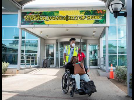 A worker is seen wearing gloves and a protective mask as he provides wheelchair assistance to an elderly traveller at the arrivals area of the Norman Manley International Airport on Tuesday. Staff were provided with protective gear as Jamaica ramped up its safety protocol at all ports of entry amid a global coronavirus outbreak.