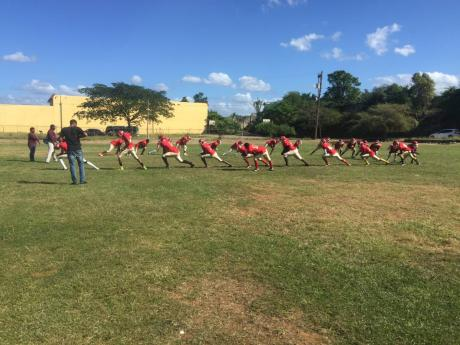Newell High School's tackle football players engage in warm-up drills recently, ahead of their upcoming National Gridiron Championship game against Munro College at the UWI Mona Bowl tomorrow.