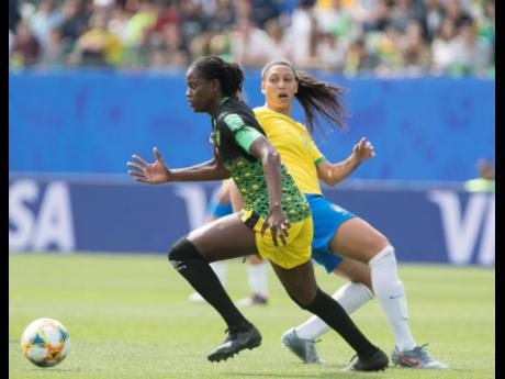 File Reggae Girl Konya Plummer (left) was forced off the field by an injury early in the second half.