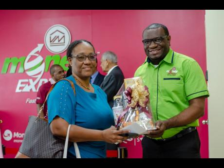 Michael Howard (right), chief executive officer, Victoria Mutual Money Transfer Services, presents a token to Carole Brown, VM Money Express, Savanna-La-Mar's first customer, at the grand opening of the location on January 31  in Westmoreland.