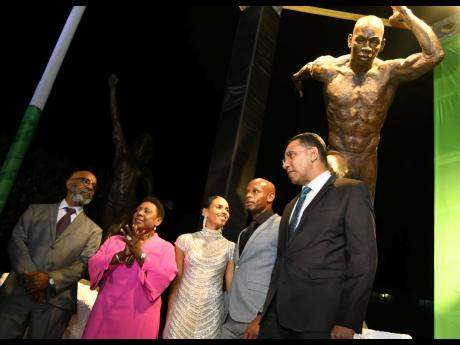 Olympian Asafa Powell (second right) poses with wife Alyshia (centre), sculptor Basil Watson (left), Sports Minister Olivia Grange (second left) and Prime Minister Andrew Holness in front of his statue which was unveiled at Independence Park on Sunday evening.