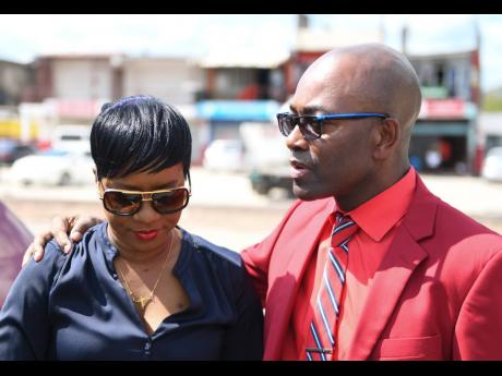Teacher Marsha Lee Crawford is greeted by Owen Speid, president of the Jamaica Teachers' Association, who came out with other members of the JTA to support her on the first day of her disciplinary hearing at Pembroke Hall High School last month.