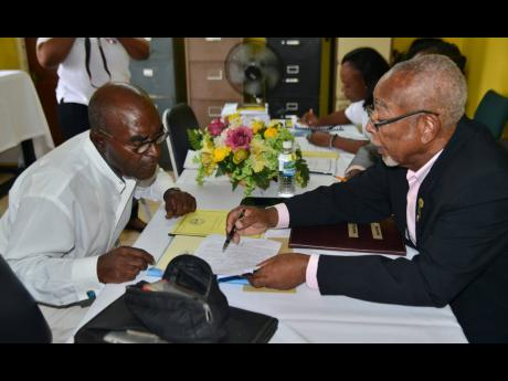 Independent candidate Derrick Lambert (left) is assisted by returning officer Winston Thomas during his nomination at Vere Technical High in Clarendon South East last Wednesday.