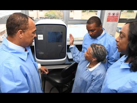 Dr Christopher Tufton (left), minister of health and wellness, listens as Dr Monica Smikle (second right), head of the National Influenza Centre, discusses the capacity of a coronavirus testing machine during a tour of the facility at The University Hospital of the West Indies yesterday. Looking on are Dr Michelle Hamilton (right), acting director of the National Laboratory Services, and Dr Carl Bruce, medical chief of staff and consultant neurosurgeon of UHWI.