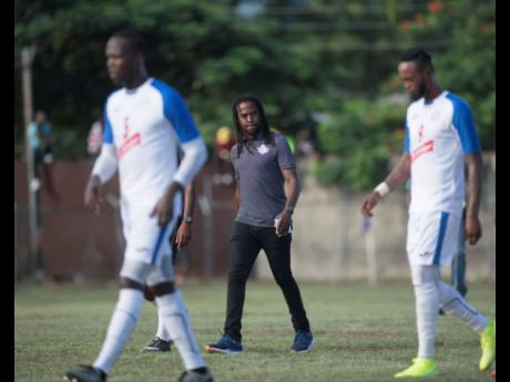 Portmore United coach Ricardo Gardner (centre) walks across the field at half time during a Red Stripe Premier League match against Dunbeholden at the Spanish Town Prison Oval earlier this season.