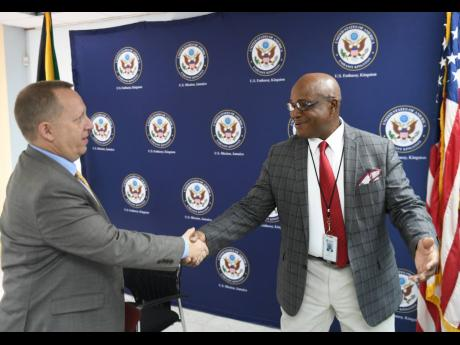 Deputy chief of mission of the United States Embassy, John McIntyre, (left) shakes hands with retired Lieutenant Colonel Gary Rowe, commissioner of corrections, at the handover ceremony of the Polygraph Unit to the Department of Correctional Services by the Embassy of the United States in Jamaica.