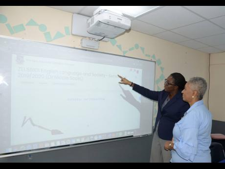 Dr Nicole Scott, deputy dean of the Graduate School of Education, The Mico University College, demonstrates the use of a smart projector to Sharon Wolfe, director of alumni affairs and development, at the official launch of the college's SMART Room on Tuesday.
