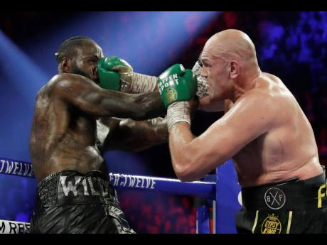 Tyson Fury (right) of England lands a right to Deontay Wilder during a WBC heavyweight championship match in Las Vegas, Nevada, on Saturday.