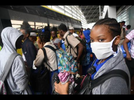 Students wear protective gear against the spread of the novel coronavirus at the Half-Way Tree Transportation Centre on Wednesday. Two cases of COVID-19 have been confirmed in Jamaica.