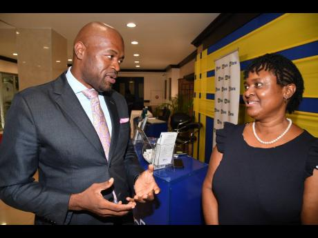 Chairman of the Jamaica Police Federation (JPF), Sergeant Patrae Rowe makes a point to Sharon Smith, head of the JN Individual Retirement Scheme, during a symposium organised by the JPF recently for rank and file cops.