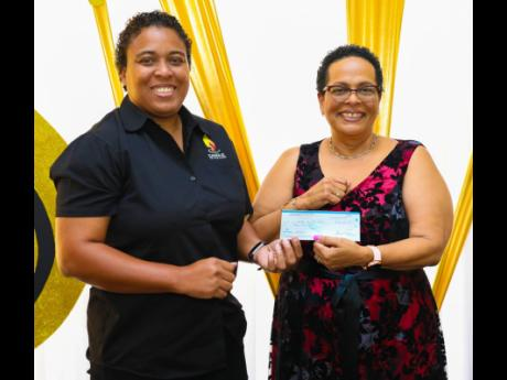 Wendy Freckleton (left), chairman of Candle in the Dark, accepts a cheque valued at $50,000 from Dale Greaves-Smith, branch manager of Sagicor Life Jamaica Mandeville, during an awards ceremony held by the branch on March 12 at the Moreland Estate Clubhouse in Manchester. Sagicor Life's Field Managers' Association also committed $200,000 to the charity, which supports the homeless and mentally challenged in the parish.