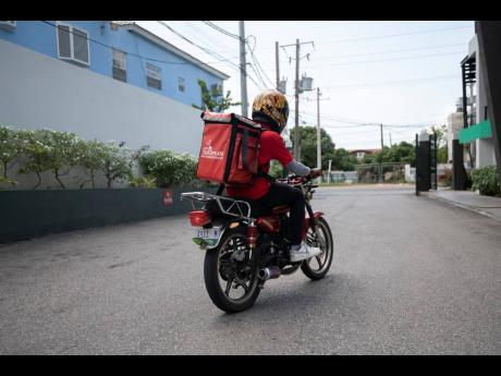 A QuickPlate motorcyclist exits 80 LMR in St Andrew on Wednesday. The food-delivery outfit has noticed an increase in user registration amid the local spread of COVID-19 in Jamaica and intends to launch a grocery-delivery offering early next week.