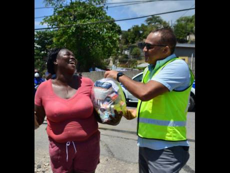 Natalie Palmer of Shooters Hill is happy to receive a care package from Dr Christopher Tufton, minister of health and wellness, in the Seven Miles area of Bull Bay. St Andrew, on Wednesday. Seven Miles and Eight Miles have been quarantined because the first COVID-19 patient had contact with the area.