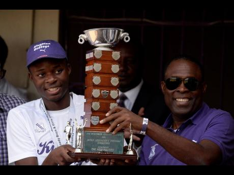 Tarees Rhoden (left), Captain of Kingston College's 2019 Track Team and Head Coach Leaford Grant (right) show off the Mortimer Geddes Trophy during their 2019 Champs celebration held at Kingston College on April 1, 2019.