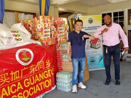 Leo Fung of the Jamaica Gangdong Association (left) and Mayor of St Ann's Bay, Michael Belnavis, touch elbows after the Chinese group handed over goods valued $700,000 to the St Ann Municipal Corporation on Thursday.