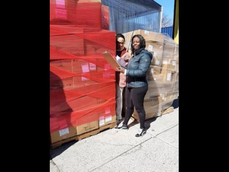 American Friends of Jamaica Executive Director Caron Chung and volunteer Keisha Lawrence prepare the shipment of personal protective equipment for delivery to Jamaica.