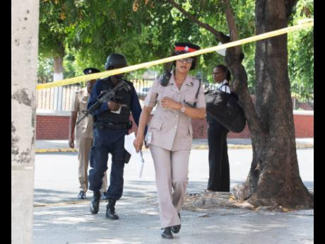 Members of the Jamaica Constabulary Force at the cordoned crime scene where an alleged thief was shot dead on Monday, March 23, at East Parade in the vicinity of Coke Memorial Methodist Church.