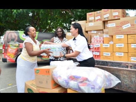 Andrinne Grant from Save Our Boys and Girls Foundation receives a case of water from Laura Loshusan (right), director of Progressive Grocers, while Nadine Mullings looks on. Progressive Grocers was making a donation to the foundation on Monday as part of the COVID-19 relief measures.