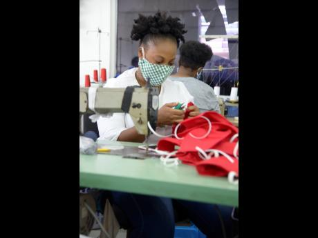 Sobrena Powell, embroidery assistant, cutting and stringing masks at Apparel Wearhouse on Red Hills Road, St Andrew.