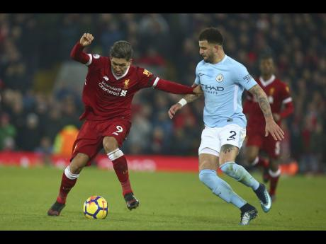 Manchester City's Kyle Walker (right) hassles Liverpool's Roberto Firmino for the ball during their English Premier League match at Anfield Stadium, in Liverpool, England on Sunday, January 14, 2018.