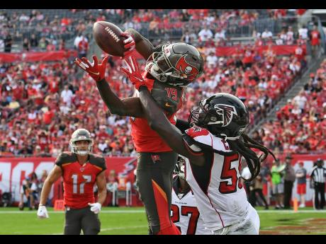 Tampa Bay Buccaneers wide receiver Breshad Perriman (centre) pulls in a 24-yard touchdown reception in front of Atlanta Falcons outside linebacker De'Vondre Campbell (right) during the first half of an NFL football game in Tampa, Florida on Sunday, December 29, 2019.